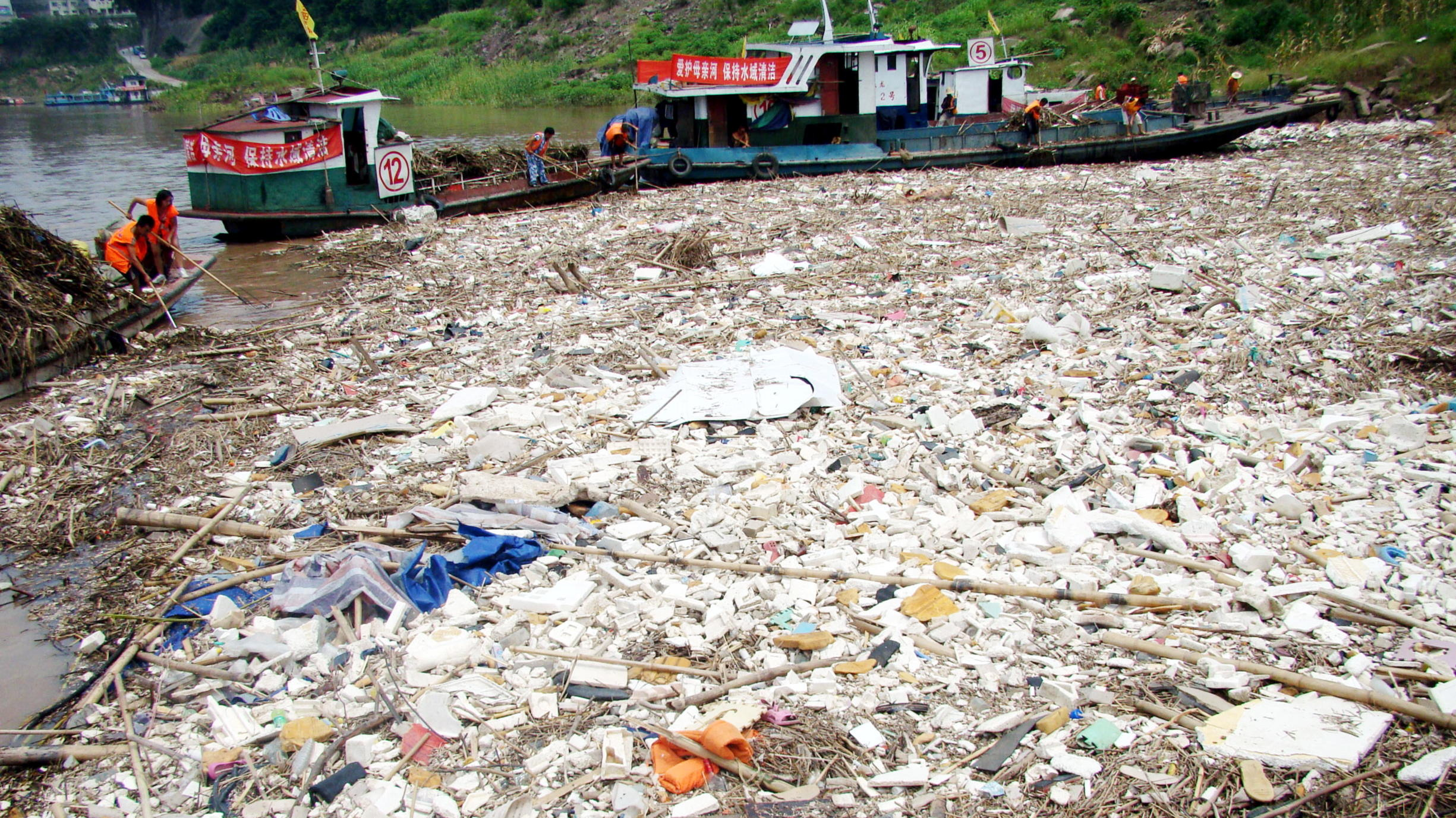 Chinese workers clean up trash floating on the Yangtze River in the Three Gorges reservoir in Yunyang county, Chongqing, China, 25 July 2010. An alarm over massive environmental damage along the Yangtze River and its Three Gorges reservoir has been r