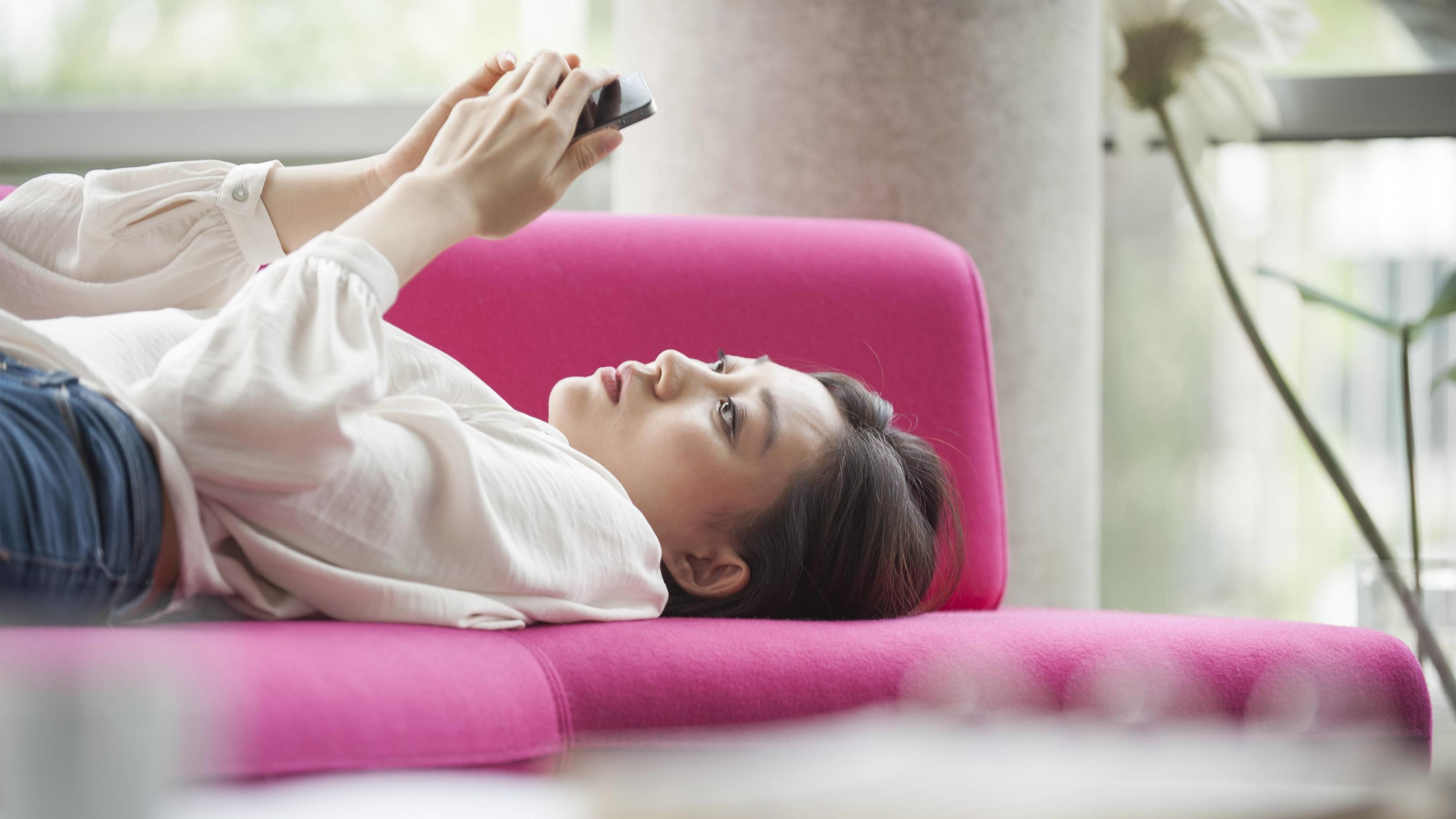 Woman relaxing at home using smartphone PUBLICATIONxINxGERxSUIxAUTxONLY Copyright: OdilonxDimier B27279227
