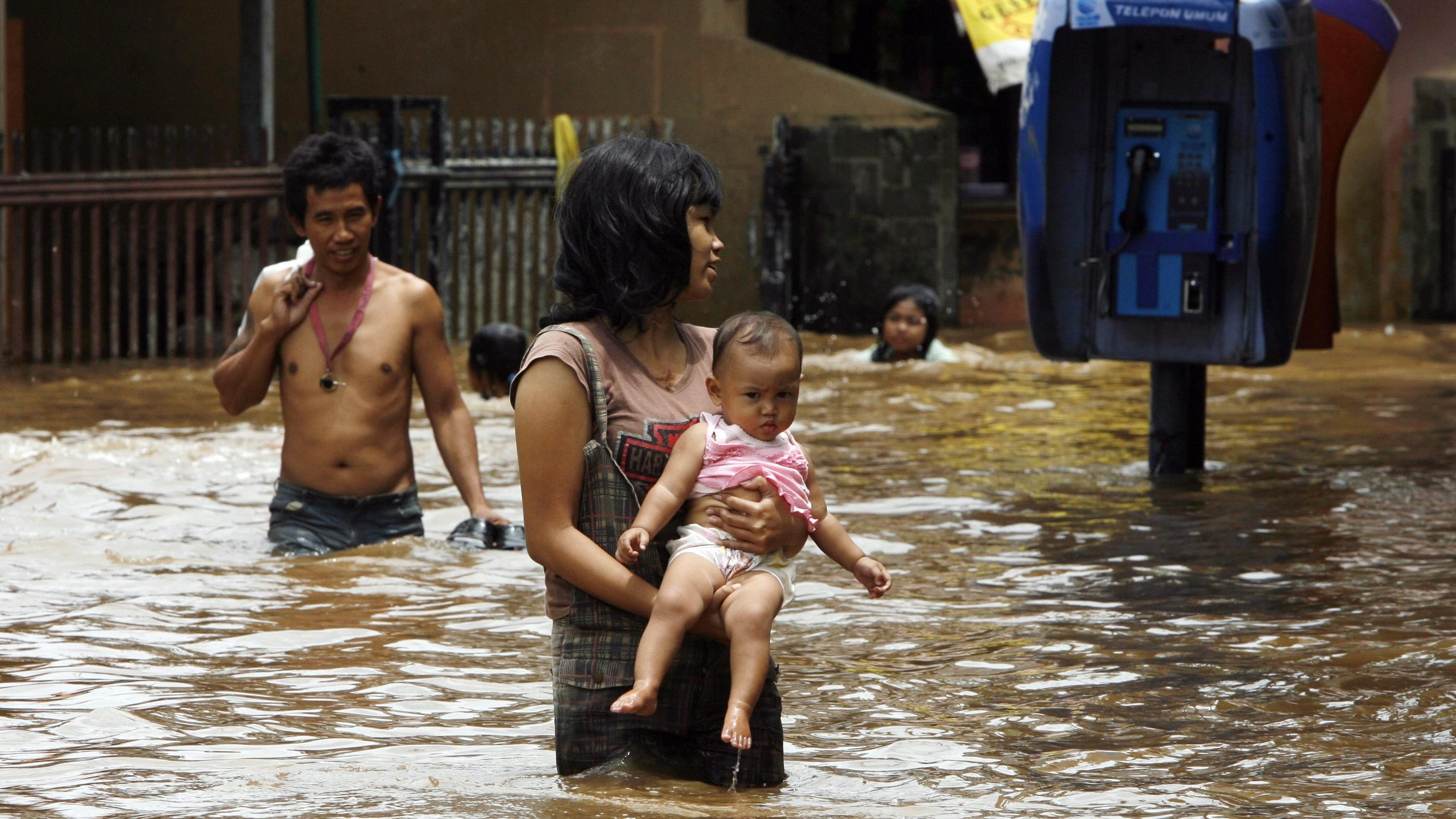 An Indonesian woman carries her daughter as she wades through a flooded residential area in Jakarta, Indonesia, 19 February 2010. Floodwater from the overflowing Ciliwung River has inundated a number of areas in Southern and Eastern parts of the capi