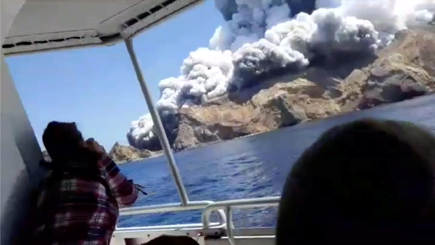 People on a boat react as smoke billows from the volcanic eruption of Whakaari, also known as White Island, New Zealand December 9, 2019 in this picture grab obtained from a social media video. INSTAGRAM @ALLESSANDROKAUFFMANN/via REUTERS THIS IMAGE H