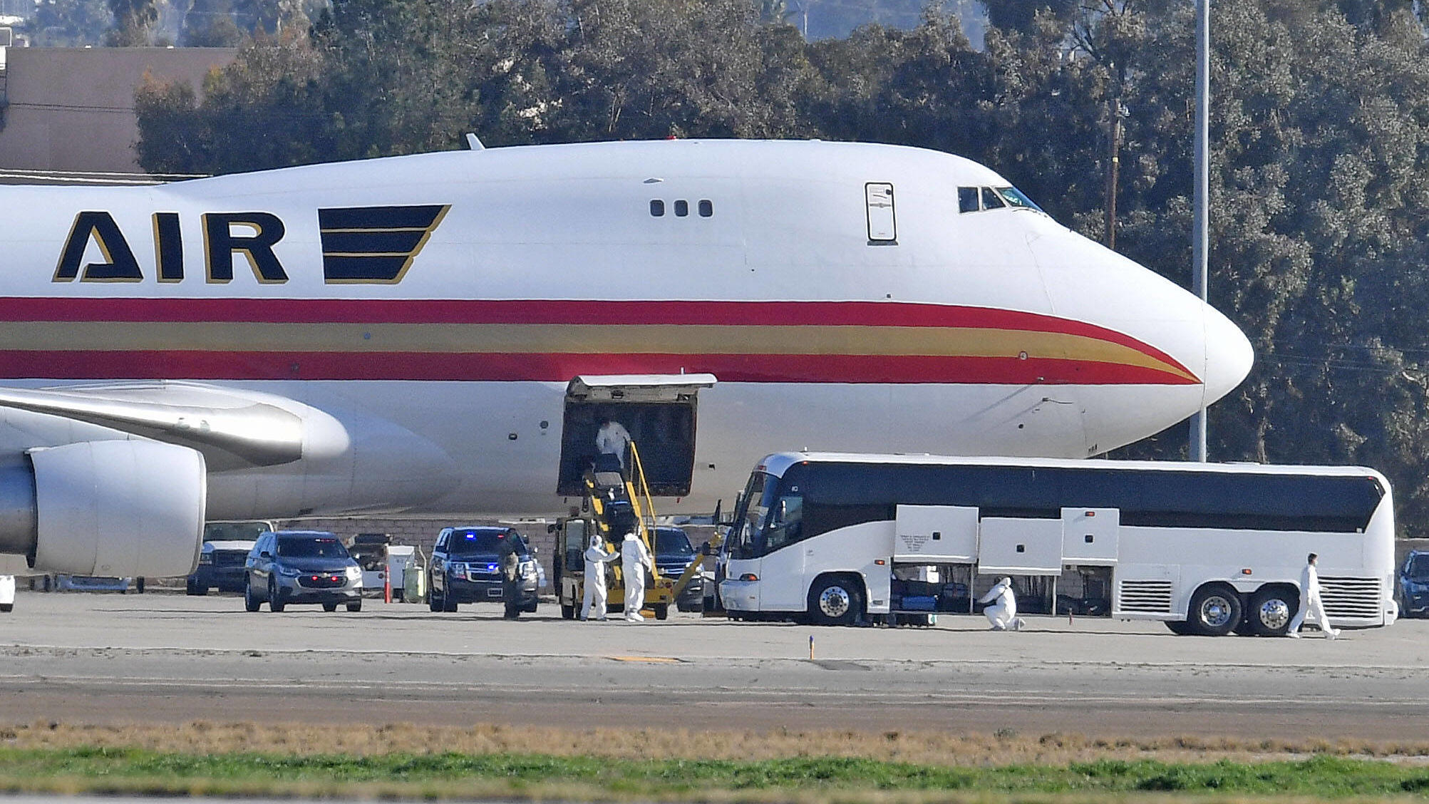 January 29, 2020, Riverside, California, USA: A team in white biohazard suits unload luggage off a charter flight from Wuhan, China, carrying approximately 200 U.S. citizens, after landing at March Air Reserve Base in Riverside, Calif. Wednesday morn