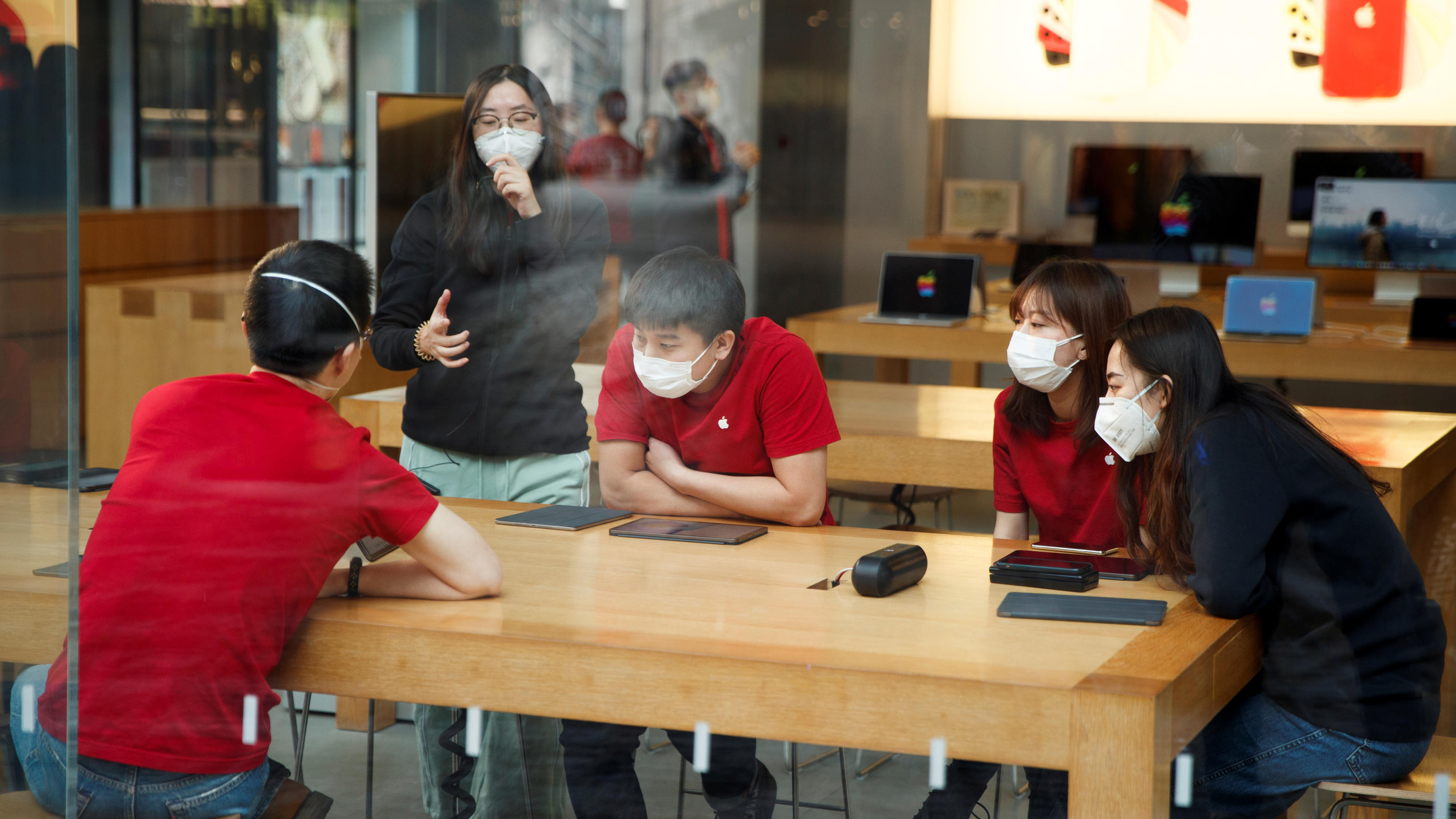People wear face masks as they listen to a presentation in an Apple Store in the Sanlitun shopping district in Beijing as China is hit by an outbreak of the new coronavirus, January 25, 2020. Picture taken January 25, 2020.   REUTERS/Thomas Peter