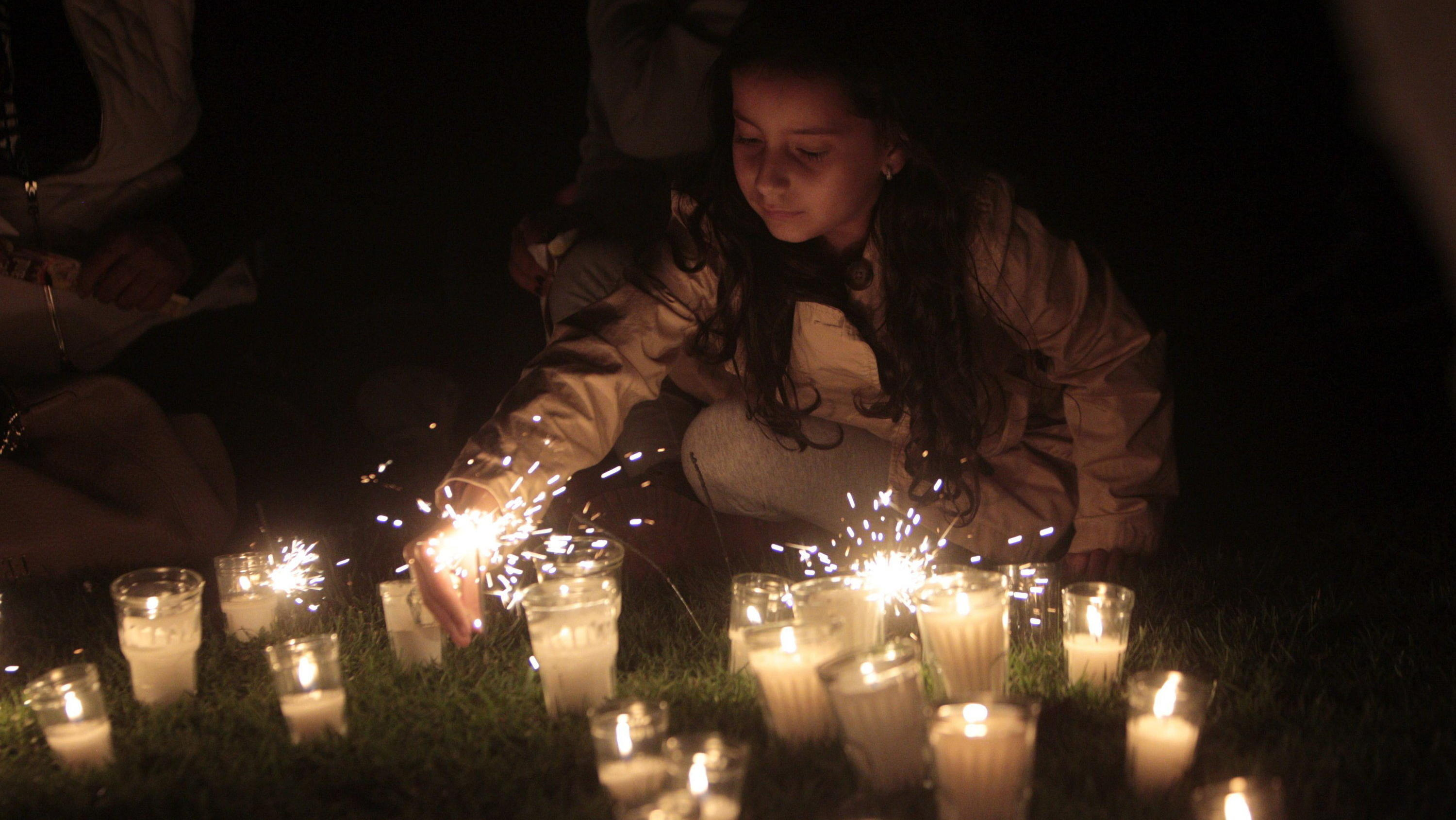 epa04684748 A girl places a candle during the 'Earth Hour' event in Guatemala City, Guatemala, 28 March 2015. Earth Hour takes place worldwide at 8.30 pm local time and is a global call to turn off lights for 60 minutes to raise awareness of the dang