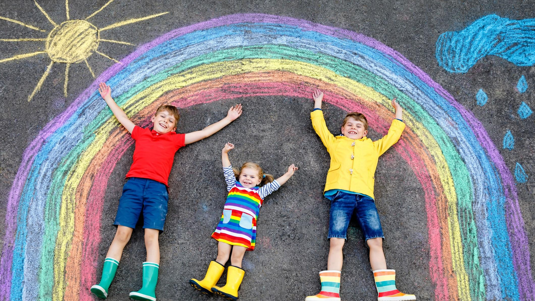 three little children, two school kids boys and toddler girl having fun with with rainbow picture drawing with colorful chalks on asphalt. Siblings in rubber boots painting on ground playing together