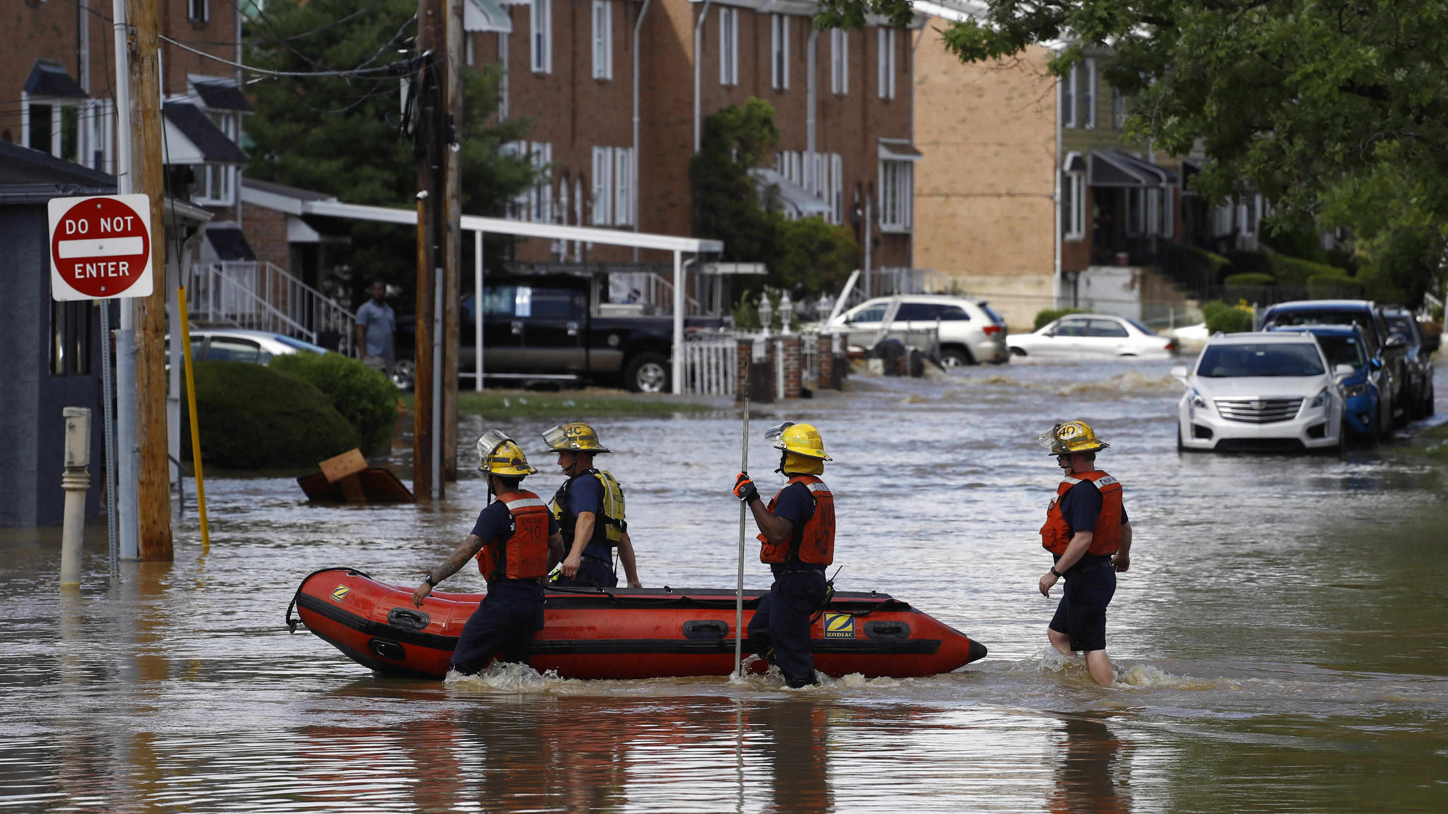 Philadelphia firefighters walk through a flooded neighborhood after Tropical Storm Isaias moved through, Tuesday, Aug. 4, 2020, in Philadelphia. The storm spawned tornadoes and dumped rain during an inland march up the U.S. East Coast after making la