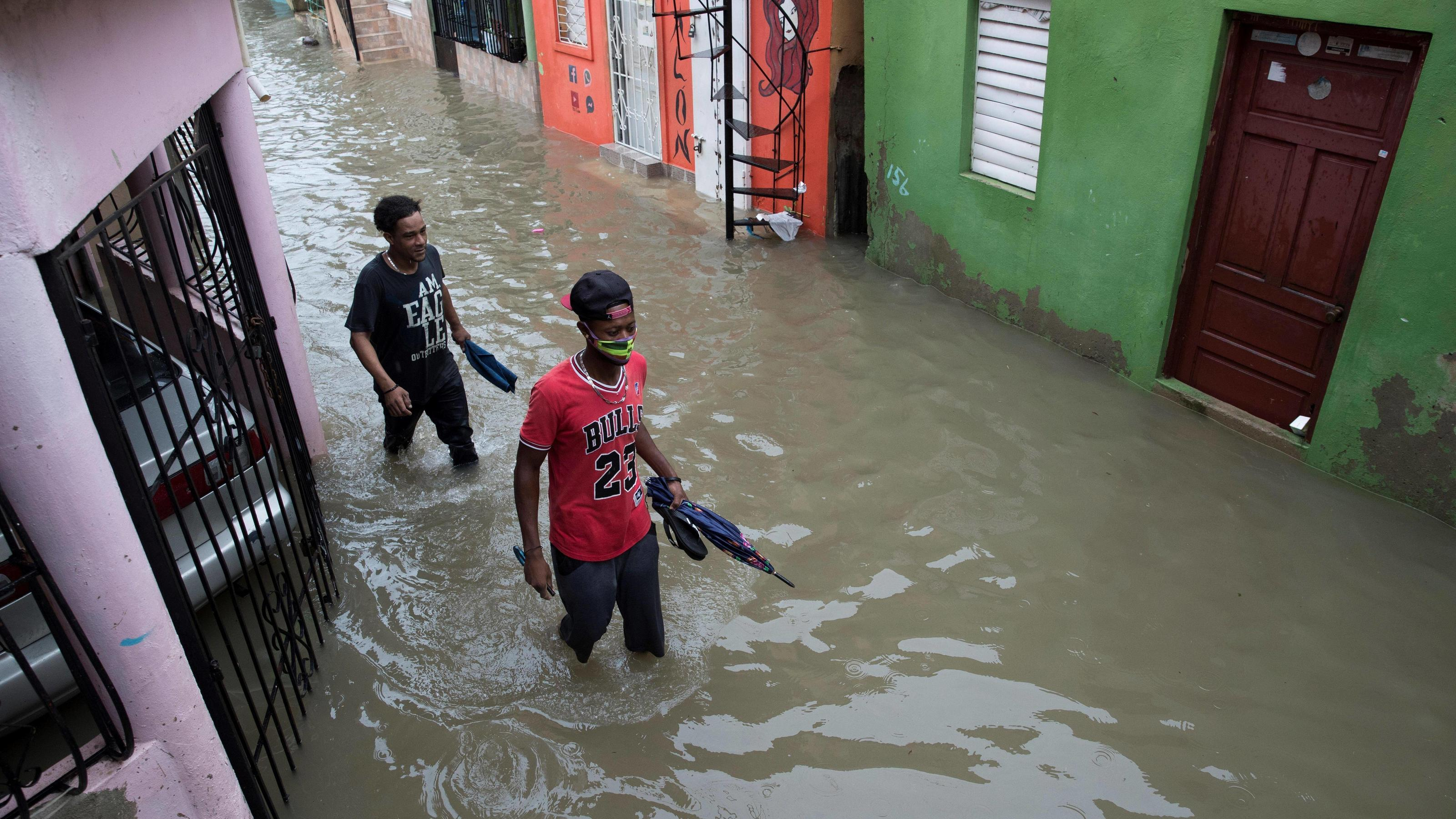 People walk on a completely flooded street due to heavy rains from Storm Laura, in Santo Domingo, Dominican Republic, 23 August 2020. At least three people died this Sunday in the Dominican Republic due to torrential rains caused by Tropical Storm L