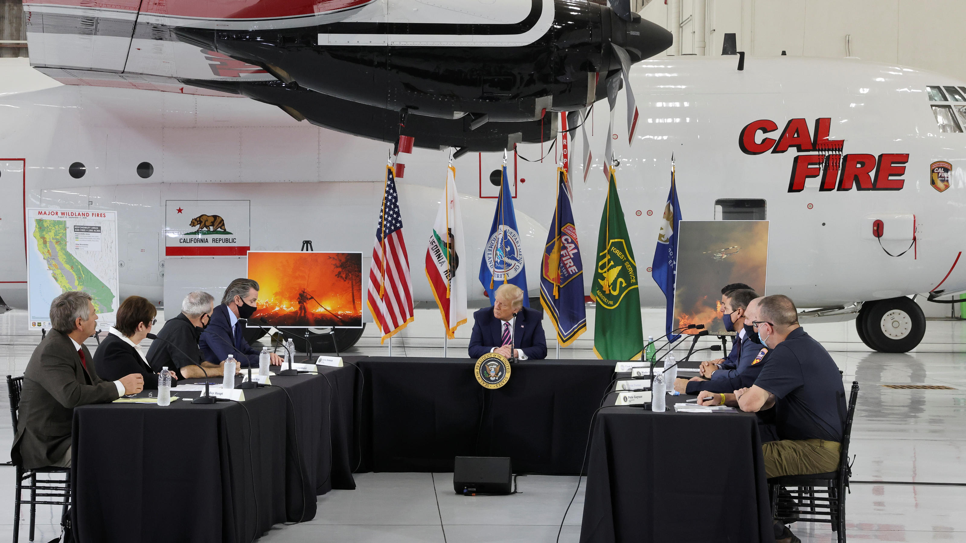 U.S. President Donald Trump sits in front of a CAL FIRE firefighting aircraft as California Governor Gavin Newsom speaks during a briefing on wildfires in McClellan Park, California, U.S., September 14, 2020. REUTERS/Jonathan Ernst