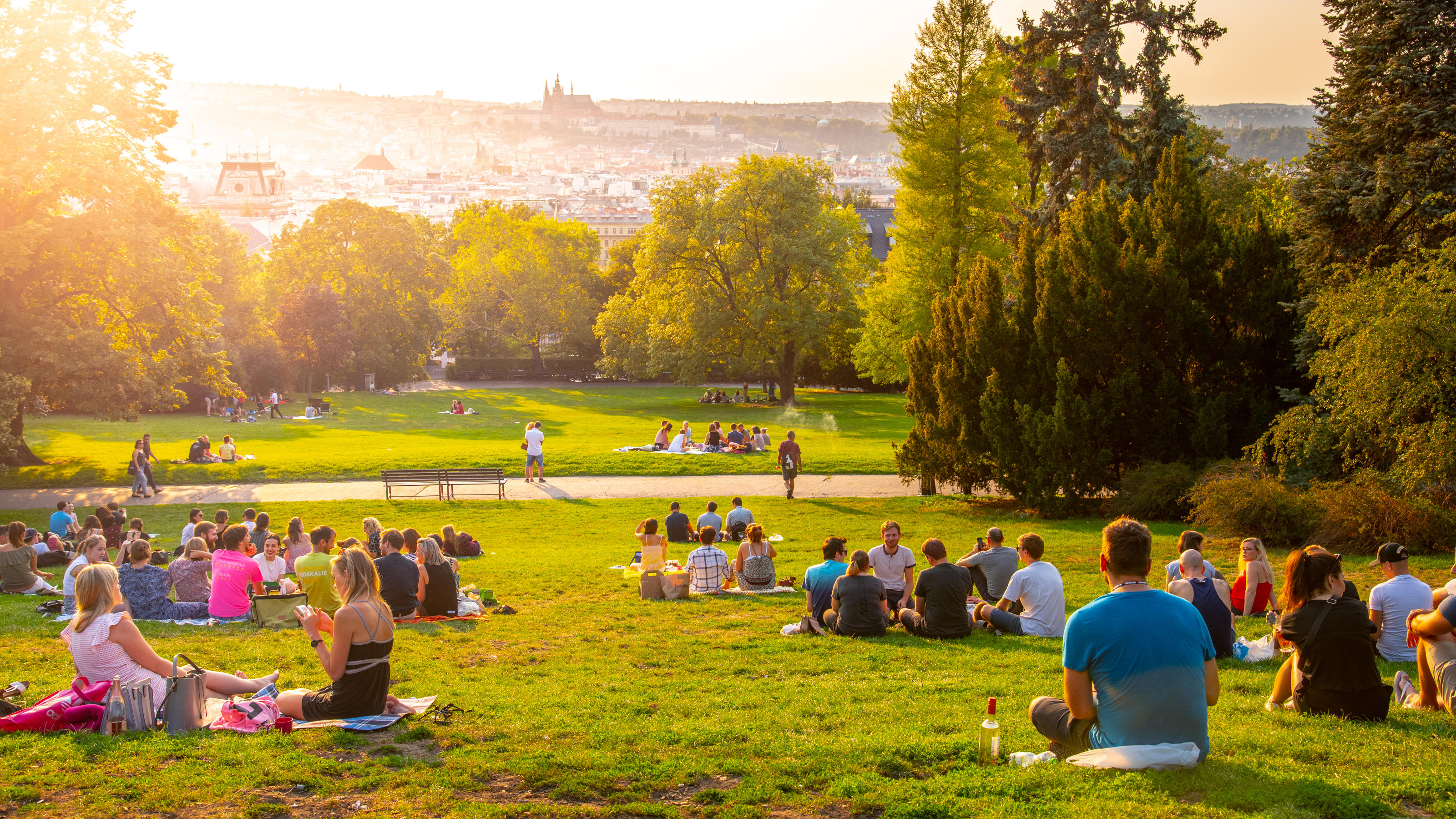 PRAGUE, CZECH REPUBLIC - AUGUST 17, 2018: Sunset in Rieger Gardens, Riegrovy sady, in Prague. Many people sitting in the grass and enjoying sunny summer evening and lookout of Prague historical city centre. Czech Republic.