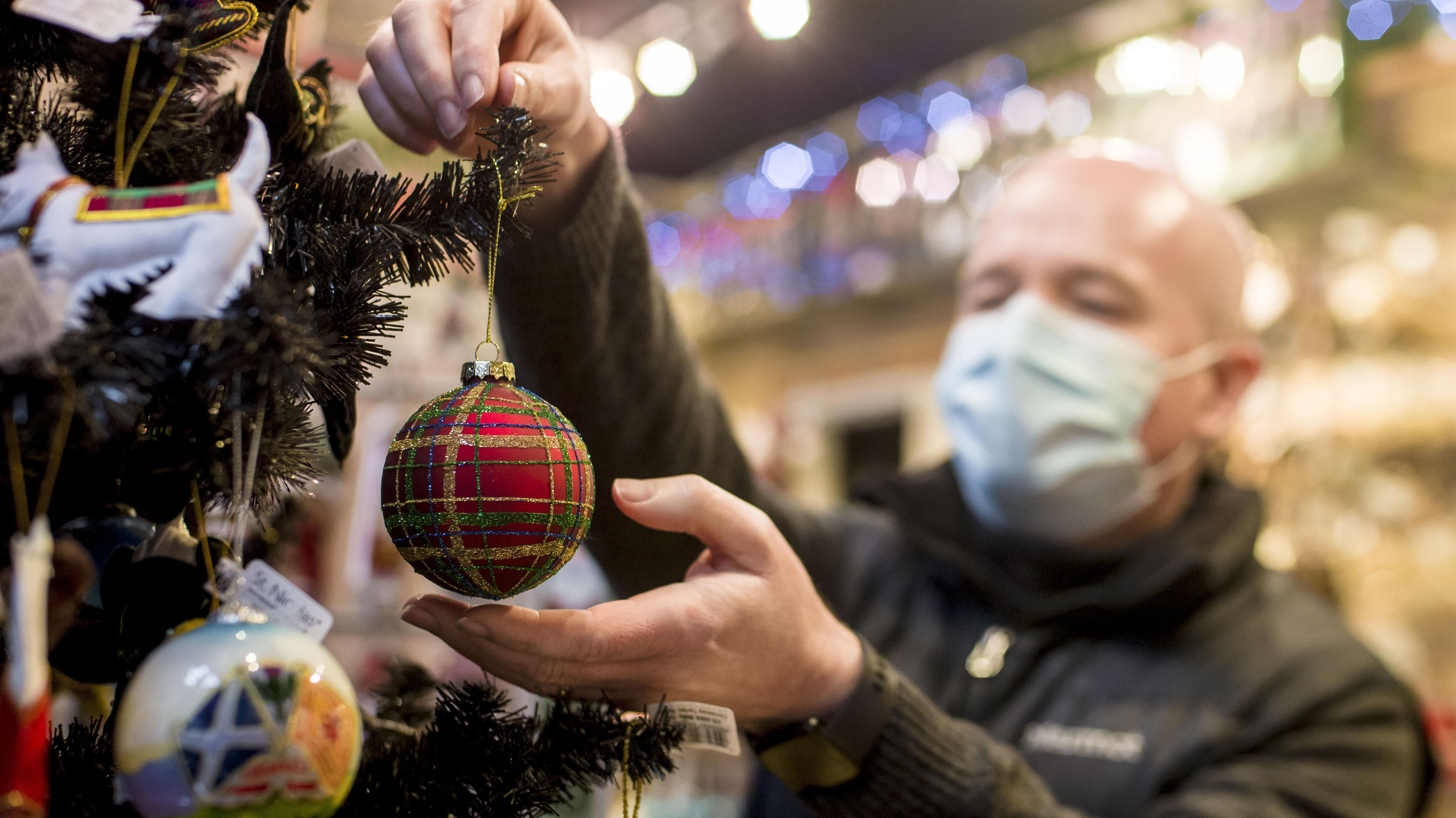 Chris Smyth owner of Ye Olde Christmas Shoppe in Edinburgh hangs a decoration on a Christmas tree in his shop, as Mr Leitch said people should
