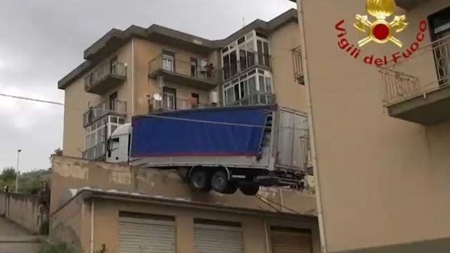 Diese Bilder sind so einfach nicht zu erklären. Im italienischen Caccamo ist ein Lkw nach einem Unfall auf einem Haus gelandet. Die Feuerwehr versucht, das schwere Fahrzeug mit zwei Kränen zu bergen.