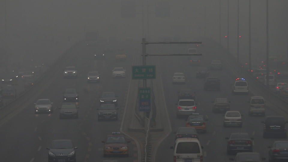 FILE - epa05078545 Vehicles travel through a main thoroughfare during a hazy day in Beijing city, China, 22 December 2015. Beijing issued a red alert for smog on 18 December 2015, urging schools to close and residents to stay indoors for the second t