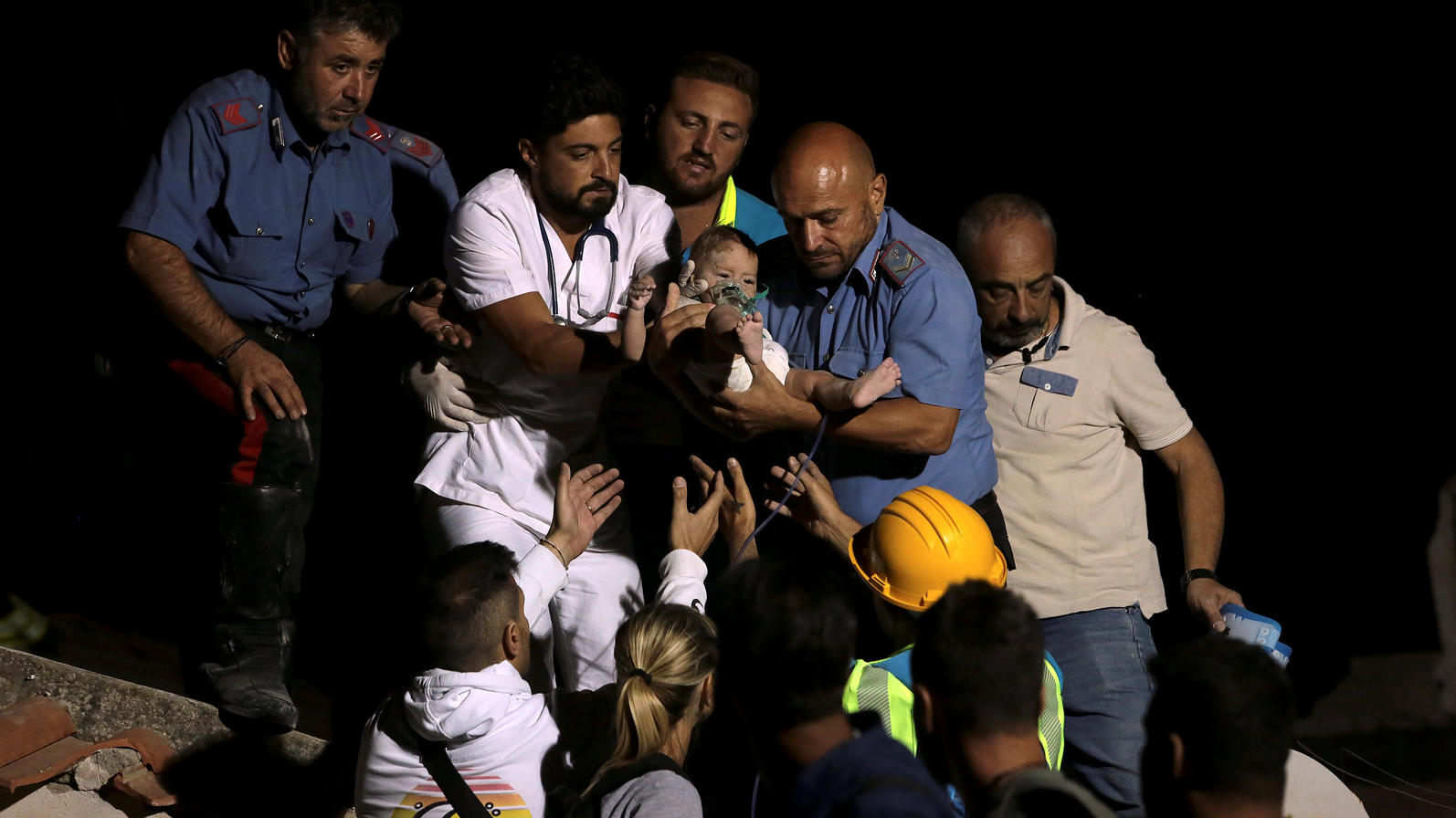 Italian Carabinieri police officer and a doctor carry a child after an earthquake hit the island of Ischia, off the coast of Naples, Italy August 22, 2017. REUTERS/Antonio Dilaurenzo NO RESALES. NO ARCHIVE