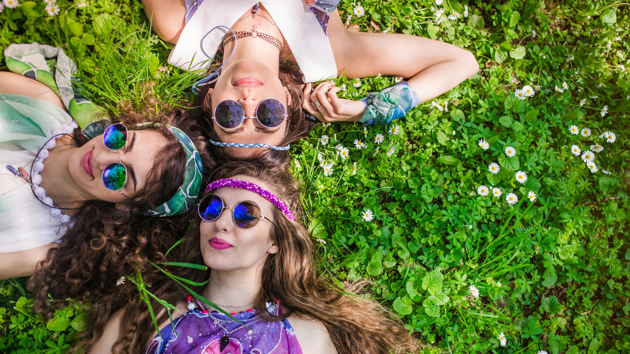 Beautiful girls of hippie laying on the grass and daisy flowers
